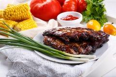 Costillas de cerdo asadas a la parilla Las costillas del Bbq de la carne sirvieron con la salsa y las verduras frescas fotos de archivo