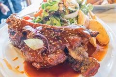 Costillas de cerdo asadas a la parrilla en la placa blanca adornada con la ensalada y la patata frita fotografía de archivo libre de regalías