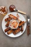 Costillas de cerdo asadas a la parrilla en salsa y miel de barbacoa con la chucrut y la cerveza en una placa blanca Bocado a la c fotos de archivo
