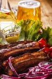 Costillas de cerdo asadas, verduras frescas y un vidrio de cerveza en una tabla de madera Fotografía de archivo libre de regalías