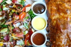 Costillas de cerdo asado con la salsa de barbacoa y la ensalada de fruta fotografía de archivo