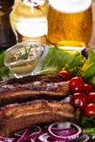 Costillas de cerdo cocidas con las verduras, la mostaza y un vidrio de cerveza en una tabla de madera Imagen de archivo libre de regalías