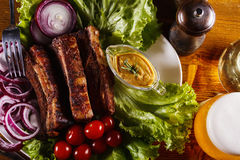 Costillas de cerdo cocidas con las verduras, la mostaza y un vidrio de cerveza en una tabla de madera Foto de archivo