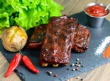 Costillas de cerdo fritas y con las patatas, las pimientas de chile y las hojas cocidas en una bandeja de piedra negra, primer de Foto de archivo libre de regalías