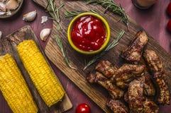 Costillas fritas deliciosas del cordero asadas a la parrilla con la salsa, las hierbas y el maíz picantes en cierre rústico de ma Foto de archivo