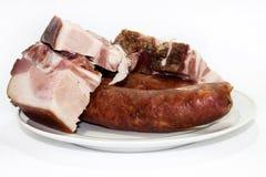 Costillas y salchichas de cerdo en la placa Imagen de archivo libre de regalías