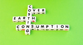 Costing the Earth. Concept ' over consumption is costing the Earth ' set out crossword style with letters on small white cubes on a green background Stock Photos