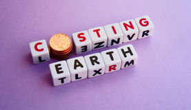 Costing the Earth. Text ' costing ' the ' Earth ' in uppercase letters on small white cubes with letter ' o ' replaced by penny coins Stock Photo