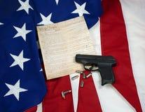 Costituzione con la pistola & le cartucce della mano sulla bandiera americana Fotografia Stock
