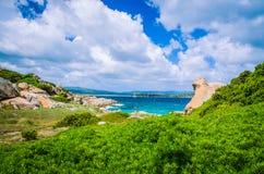 Costline用cloudscape和花岗岩岩石和天蓝色的水在波尔图Pollo,撒丁岛,意大利附近 库存照片