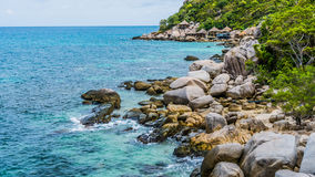 Costline of Koh Tao Islands in Thailand. Granite Rocks and blue clear water hitting Rocks Stock Image