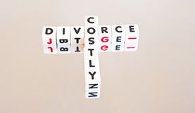 Costly divorce. Text ' costly divorce ' inscribed on small white cubes arranged in crossword fashion with common letter ' o' isolated on a bright background Stock Photo