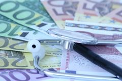 Costly medical treatment. Closeup of medical stethoscope on high denomination Euro banknotes royalty free stock images