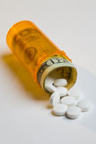 Costly medicine. Pills and money spilling out of an orange prescription bottle royalty free stock photos