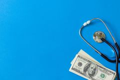 Costly treatment. Stethoscope and dollars on blue background. Medical concept. Payment for the services of a doctor. Costly treatment. stethoscope and dollars on stock photo