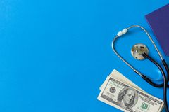 Costly treatment. Stethoscope and dollars on blue background. Medical concept. Payment for the services of a doctor. Costly treatment. stethoscope and dollars on royalty free stock photos