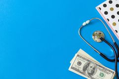 Costly treatment. Stethoscope and dollars on blue background. Medical concept. Payment for the services of a doctor. Costly treatment. stethoscope and dollars on stock photography