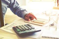 Costo calcolatore di contabilità dell'uomo di affari economico fotografie stock