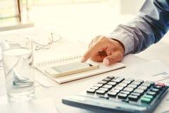 Costo calcolatore di contabilità dell'uomo di affari economico in ufficio fotografie stock