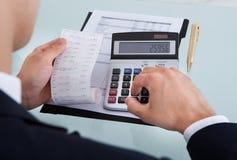 Costo calculador de Holding Receipt While del hombre de negocios en oficina Foto de archivo libre de regalías