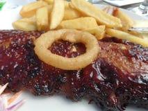 Costole appiccicose del barbecue con gli anelli delle patatine fritte, dell'insalata di cavoli e di cipolla Fotografia Stock