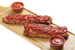 Costole arrostite col barbecue con salsa sul tagliere Immagine Stock