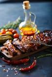 Costole arrostite col barbecue deliziose esperte con una salsa d'unto piccante e servite con tagliato Fotografie Stock