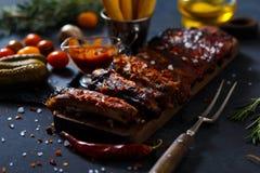 Costole arrostite col barbecue deliziose esperte con una salsa d'unto piccante e servite con tagliato Fotografia Stock