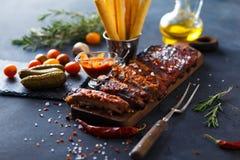 Costole arrostite col barbecue deliziose esperte con una salsa d'unto piccante e servite con tagliato Immagine Stock