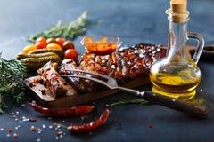 Costole arrostite col barbecue deliziose esperte con una salsa d'unto piccante e servite con tagliato Immagini Stock