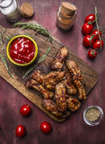 Costole arrostite saporite con salsa e le erbe piccanti su un tagliere sulla fine rustica di legno di vista superiore del fondo Fotografia Stock Libera da Diritti