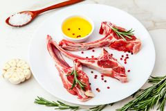 Costole crude dell'agnello con gli ingredienti per la cottura sulla tavola di marmo bianca Immagine Stock