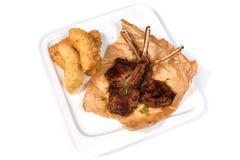 Costole dell'agnello arrostito su carta e sulle verdure in pastella in un piatto bianco su un fondo bianco isolato fotografia stock