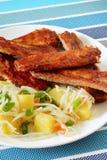Costole di carne di maiale al forno con l'insalata di patata fotografia stock