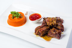 Costole di carne di maiale arrostite col barbecue servite con salsa al pomodoro e fotografia stock libera da diritti