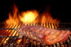 Costole di carne di maiale della parte posteriore del bambino del BBQ sulla griglia ardente calda Fotografia Stock