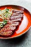 Costole di carne di maiale americane tradizionali del barbecue con un piatto laterale di insalata verde Backgroun grigio immagini stock