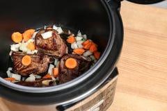 Costole di carne di maiale deliziose con le verdure in multi fornello sulla tavola di legno Spazio per testo fotografia stock