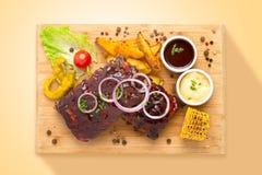 Costole di carne di maiale lustrate con le verdure alimento da sopra immagine stock