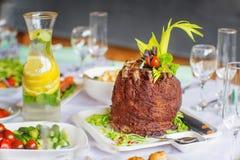 Costole di carne di maiale rotolate con le verdure sulla a con il piatto su una tavola immagine stock