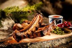 Costole di maiale del verro del BBQ servite sulla plancia di legno rustica fotografia stock