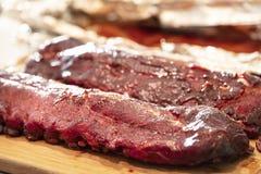 Costole di scarsità del barbecue con salsa su un tagliere immagine stock libera da diritti