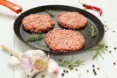 Costoletas cruas da carne org?nica com especiarias em uma frigideira em um fundo branco com alho, alecrins e pimenta imagem de stock royalty free