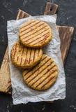 Costoletas grelhadas do hamburguer do grão-de-bico e da couve-flor do vegetariano na placa de corte de madeira em um fundo escuro Imagens de Stock Royalty Free