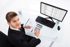 Costos calculadores del hombre de negocios en el escritorio de oficina Imagen de archivo libre de regalías
