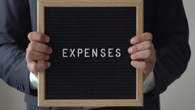 Costos de la palabra de letras en tablero del texto en el hombre de negocios anónimo Hands almacen de video