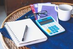Costos de las cuentas con la pluma de los vidrios de la calculadora y el libro encima del ra Fotografía de archivo
