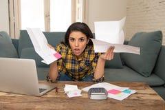 Costos de manejo de la mujer atractiva preocupante con el ordenador portátil coste de la vida y problema de las cuentas que pagan fotografía de archivo