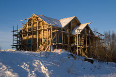 Costruction of new wood house. Sun, snow, winter royalty free stock photos