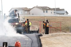 Costruction workers laying new Tarmac For New Parking Lot. Laying new tarmac for parkinlot with construction equipment stock images